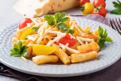 Macaroni, deegwaren in tomatensaus en kaas in een plaat op een houten lijst stock afbeeldingen