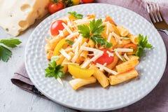 Macaroni, deegwaren in tomatensaus en kaas in een plaat op een houten lijst royalty-vrije stock foto