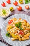 Macaroni, deegwaren in tomatensaus en kaas in een plaat op een houten lijst stock afbeelding