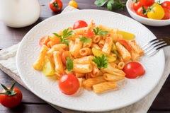 Macaroni, deegwaren in tomatensaus en kaas in een plaat op een woode royalty-vrije stock foto