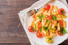 Macaroni, deegwaren in tomatensaus en kaas in een plaat op een woode stock foto