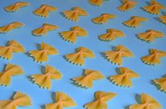 Macaroni in the form of butterflies on blue background. patterned background of pasta stock image