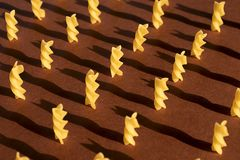 Macaroni in the form of yellow spirals on a brown background lined up and stand. Shadows royalty free stock photos