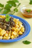 Macaroni and fry chicken hearts. On blue plate Royalty Free Stock Images