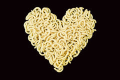 Macaroni in heart-shaped. With black backdrop Royalty Free Stock Photography