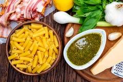 Macaroni met pesto penne rigate Met ui en bacon, kaas, basilicum, pijnboomnoten, knoflook royalty-vrije stock foto's