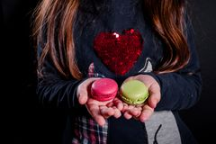 Macaroons in the palms of the girl stock photos