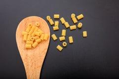 Macaroni pasta in a ladle, black background. Macaroni in a wooden ladle, black background Royalty Free Stock Photo