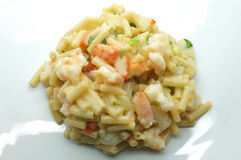 Macaroni, pasta with white cheese, shrimp, crab stick and onion Stock Image