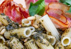 Macaroni with pesto penne rigate. With onion and bacon, cheese, basil, pine nuts, garlic. stock photography
