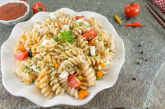 Macaroni served with cheese vegetables and parsley. Colorful meal Royalty Free Stock Images