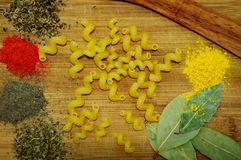 Macaroni and spices. Macaroni in the form of curls and spices: paprika, black pepper, dried basil, turmeric, fennel seeds, bay leaf on a wooden board Stock Photos
