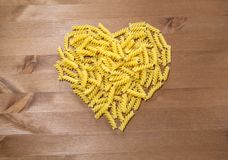 Macaroni spirals scattered on a wooden table. In the shape of a heart Royalty Free Stock Photo