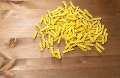 Macaroni spirals scattered on a wooden table. Pasta spirals are scattered on a wooden table. there is room for your text Royalty Free Stock Images