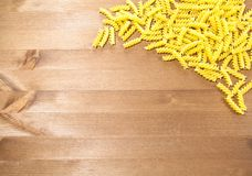 Macaroni spirals scattered on a wooden table. Pasta spirals are scattered on a wooden table. there is room for your text Stock Photo