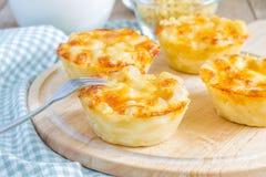 Macaronis au fromage cuits au four en tant que petits tartes image libre de droits