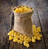 Macaronis dans le sac sur le bois photographie stock