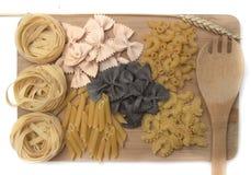 Macaronis noirs et d'or, pâtes sur un conseil en bois Photos libres de droits
