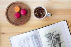 Macaronis roses et oranges de baie savoureuse fraîchement cuite au four de fruit d'un plat authentique en bois sur une table en b Images libres de droits