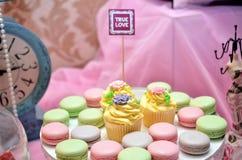 Macarons和杯形蛋糕在背景 库存照片