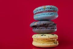 Macarons στο κόκκινο υπόβαθρο, όμορφο επιδόρπιο τρία πράγματα στη στήλη Στοκ Φωτογραφία