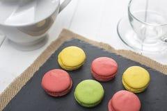 Macarons, чашка чая и чайник Завтрак с помадками Стоковое фото RF