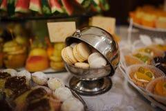 Macarons alaranjados e brancos na caçarola de aço do ferro no casamento rec Fotografia de Stock Royalty Free