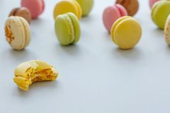 Macarons amarelos, cor-de-rosa, verdes e marrons mordidos saborosos no pa na moda Imagens de Stock Royalty Free
