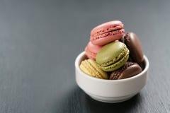 Macarons assortiti in ciotola bianca sul fondo dell'ardesia Immagini Stock