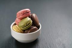 Macarons assortiti in ciotola bianca sul fondo dell'ardesia Fotografia Stock Libera da Diritti