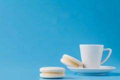 Macarons avec la tasse de café sur le fond de papier bleu images stock