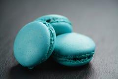 Macarons azzurrati luminosi sul fondo dell'ardesia Fotografia Stock Libera da Diritti