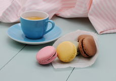 Macarons in backing paper cornet and blue Espresso cup Royalty Free Stock Images