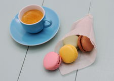 Macarons in backing paper cornet and blue Espresso cup Stock Photo