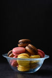Macarons in a bowl. Black background Stock Photos