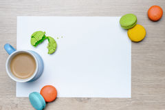Macarons breakfast frame. Cup of coffee with milk and scattered macarons as frame to blank paper Stock Photos