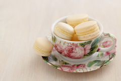 Macarons with buttercream filling in cup with rose patterns Stock Photos