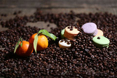 Macarons cakes among coffee beans Royalty Free Stock Photography