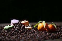 Macarons cakes among coffee beans Stock Photos