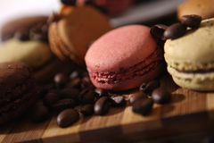 Macarons and coffee beans. Coffee beans and some macarons on a wooden trencher Royalty Free Stock Photos