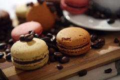 Macarons. Coffee beans and macarons on a wooden trencher Stock Images