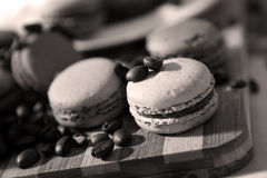 Macarons. Coffee beans and macarons on a wooden trencher Stock Photos