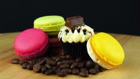 Macarons colorés délicieux avec une pile des grains de café et du petit gâteau de chocolat banque de vidéos