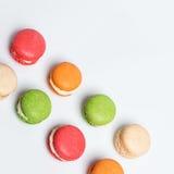 Macarons colorés d'isolement sur le blanc avec l'espace pour le texte Dessert français traditionnel Vue supérieure, configuration Photos stock