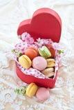 Macarons colorés dans la boîte rouge Photo stock
