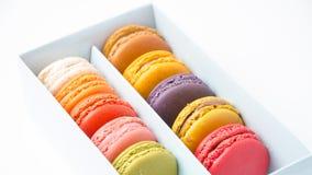 Macarons colorés dans la boîte sur le fond blanc Photographie stock