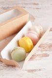 Macarons colorés dans la boîte sur le fond blanc Image stock