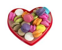 Macarons colorés dans la forme rouge de coeur d'isolement Photographie stock