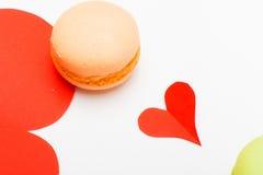 Macarons colorés français avec le coeur de papier rouge sur le backgroun blanc Photo libre de droits