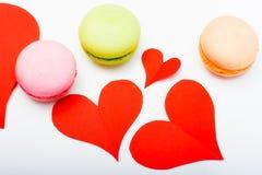 Macarons colorés français avec le coeur de papier rouge sur le backgroun blanc Photos stock